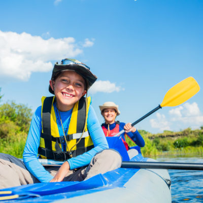 A young smiling boy and woman enjoying the river in an inflatable raft in plentiful sunshine.