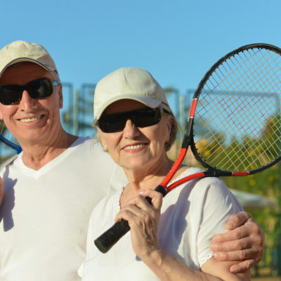 A smiling, happy couple wearing sunglasses rests between sets with tennis rackets in hand.