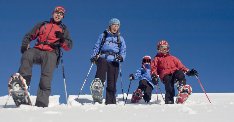 A family of four enjoys a snowshoeing excursion on a bright, sunny day.