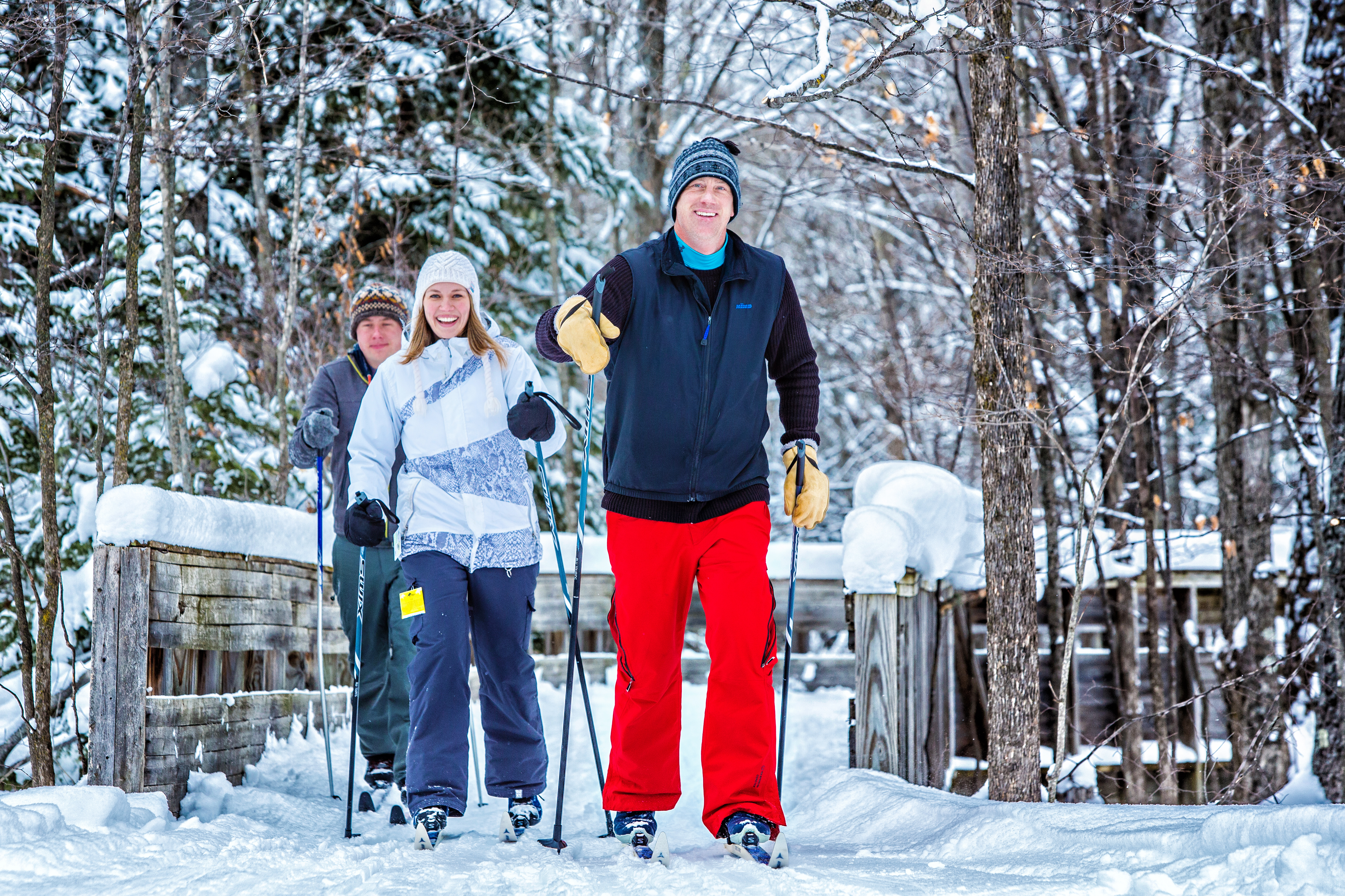 Three adults cross country skiing across a bridge on a sunny, snowy day at Treetops Resort.
