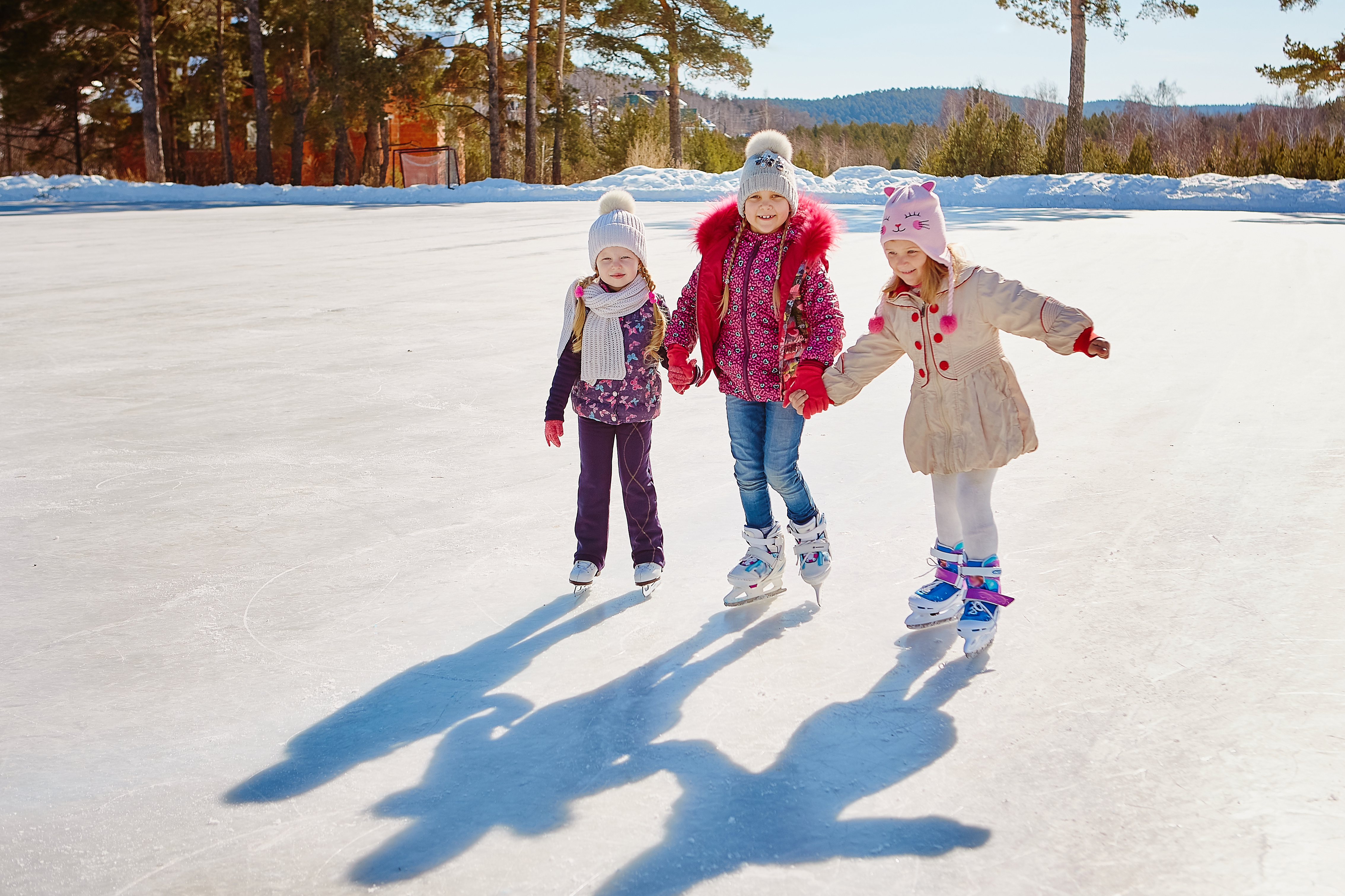 Three little girl friends learn to skate.  Outdoor recreation and holidays.