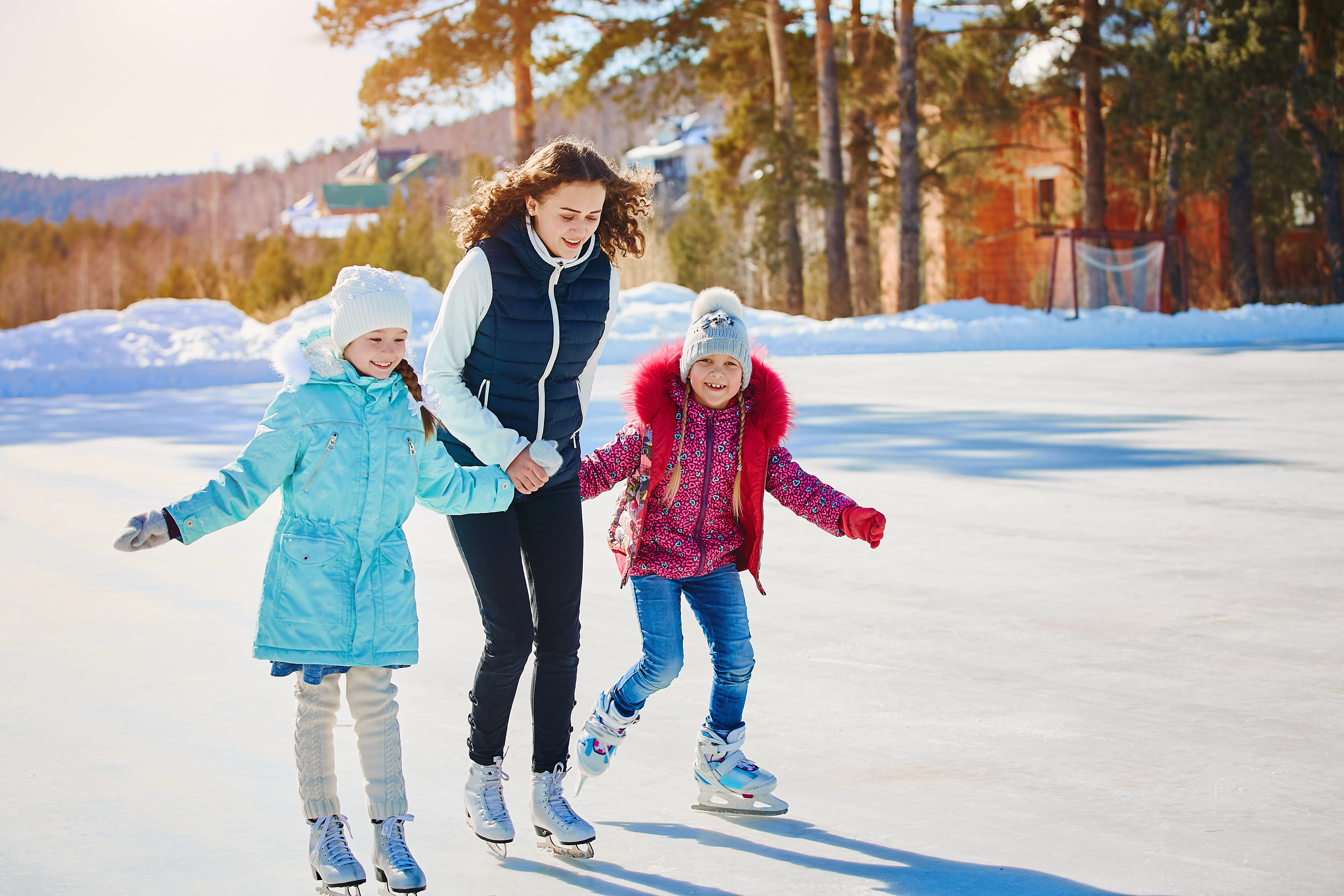 A group of three girls on a winter skating rink. Roll and laugh. Skating rink in nature