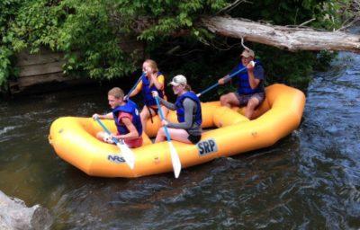 Four people enjoy a rafting trip on a Michigan river.