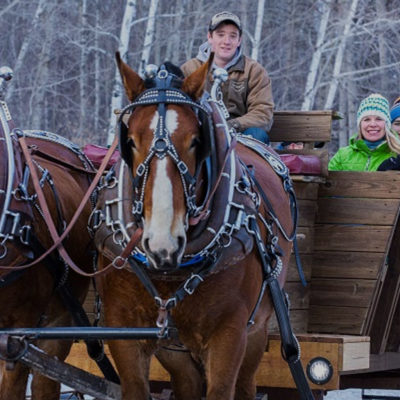 A group of people on a wooden sleigh being pulled by two horses in the snow.