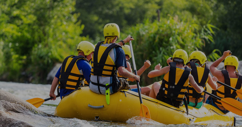 Six adults paddling a raft through the Sturgeon River rapids, the fastest river in Michigan's lower peninsula.