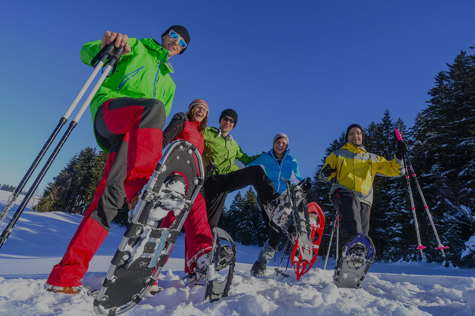 A group of people in bright winter gear raising their snow shoes up from the snow.