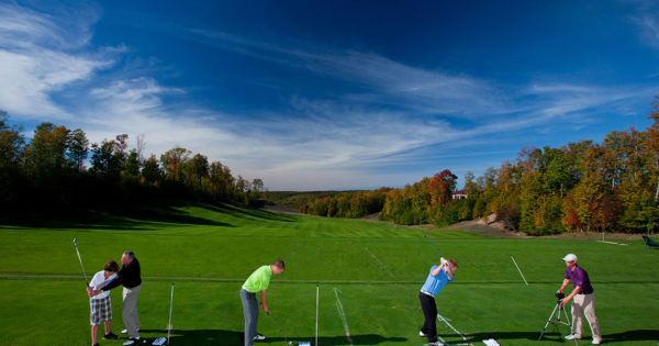 Two PGA Professional Instructors work with three golfers at the Treetops Resort driving range.