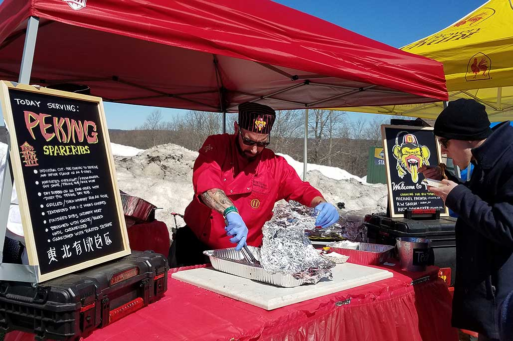 Man in red chef coat under red tent serving barbeque