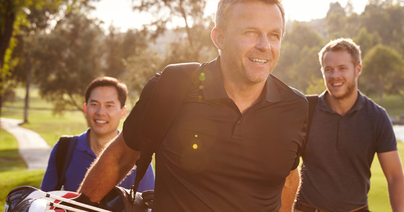 Three smiling men on a golf course on a sunny day