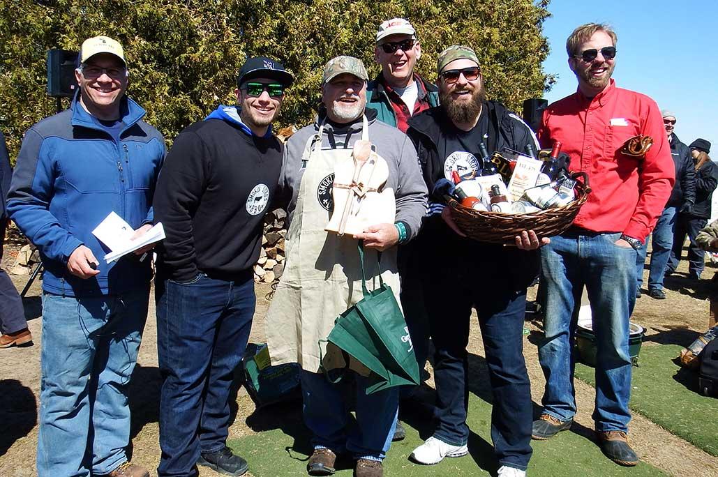 6 men in aprons holding a gift basket