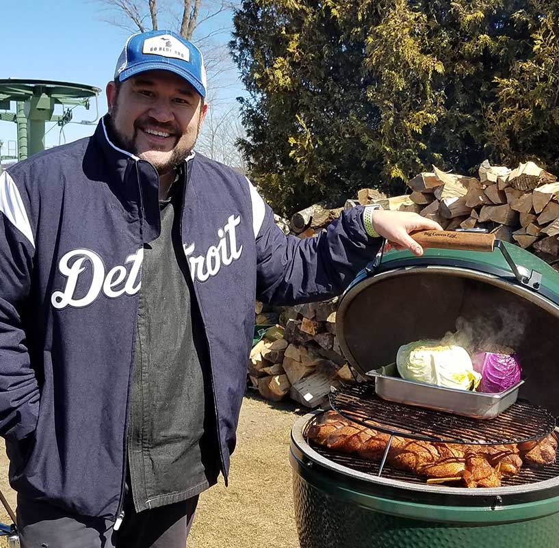 Man in blue Detroit jacket holding a green grill open