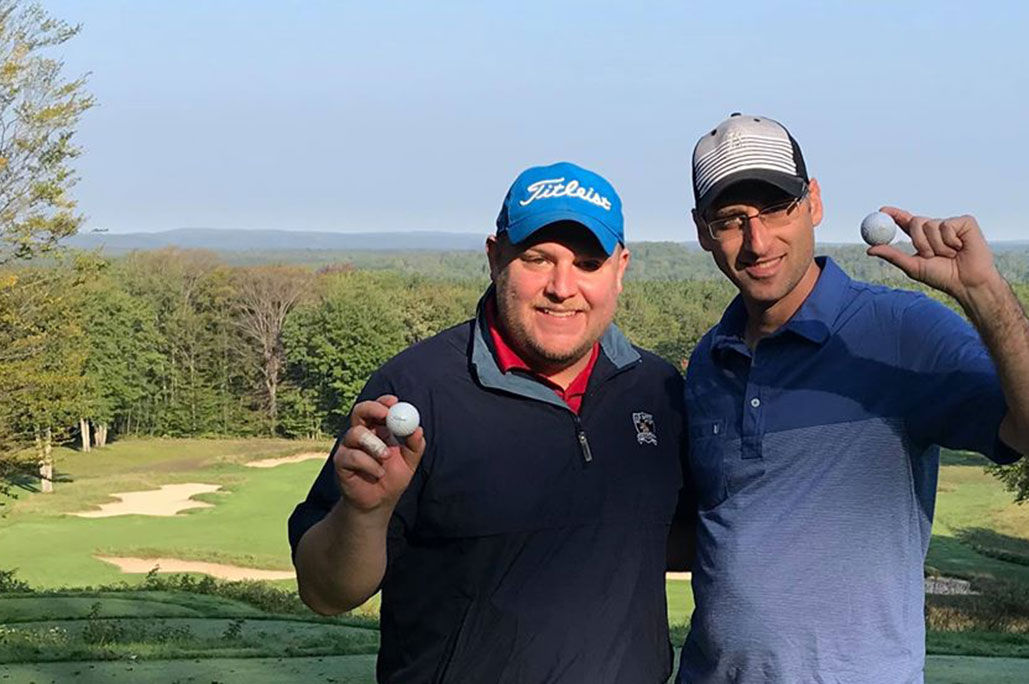 two men with hats holding golf balls