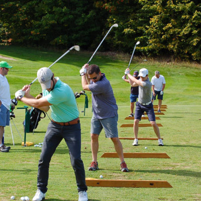 A group of golfers swing away on the Treetops golf course driving range.