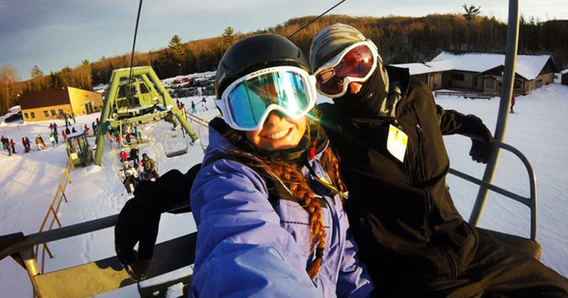 Two smiling people on a chair lift in Gaylord, MI at Treetops Resort.