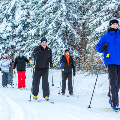 A group of people smiling while cross country skiing through the snow.