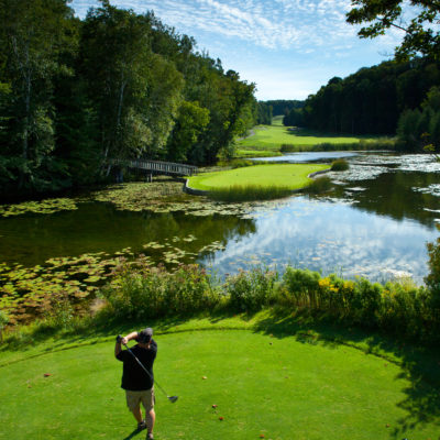 A golfer in shorts tees off on a Treetops golf course overlooking a large pond surrounded by trees.