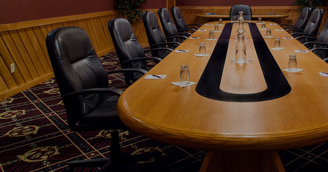 A wooden boardroom table surrounded by black office chairs.
