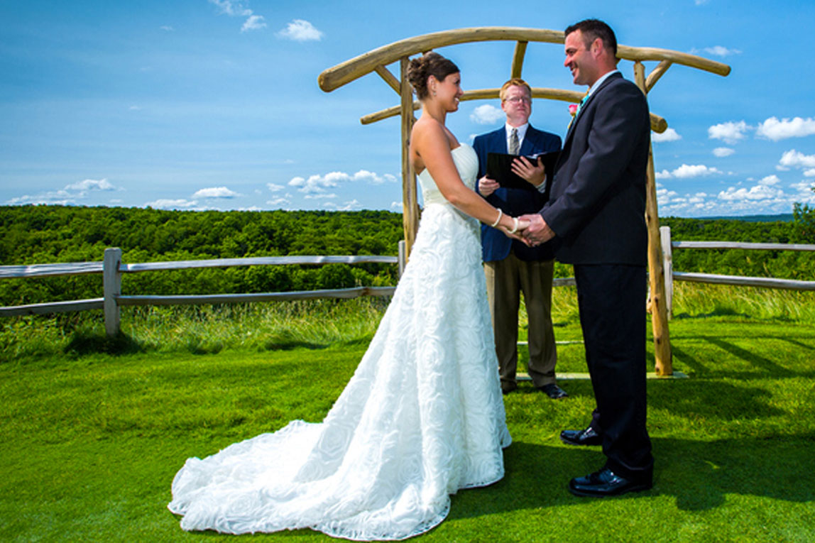 A bride, groom, and officiant stand at an arch in front of a farm fence on a bright, sunny day.