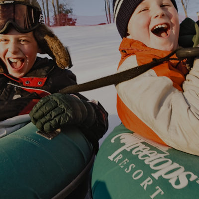 Two boys laughing while riding tubes in the snow.
