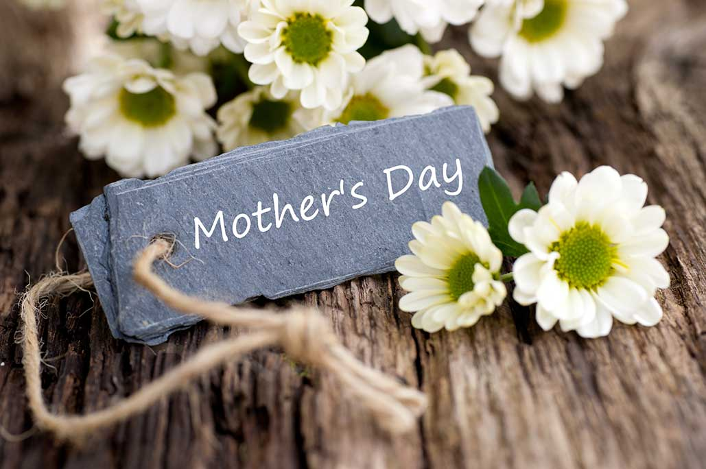 white flowers on rustic wood with Mother's Day name card