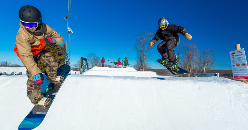 Two snowboarders hit the jumps on a sunny day at Treetops Resort.