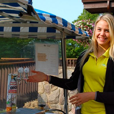 girl in yellow shirt working next to a golf beverage cart