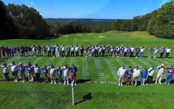 large group of golfers standing in formation around large names of fallen soldiers