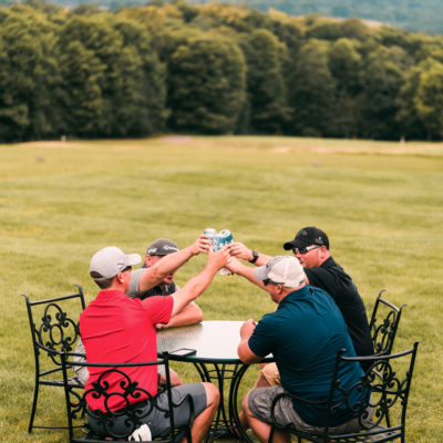 Four golfers with beers toast each other after a round of golf at Treetops Resort.