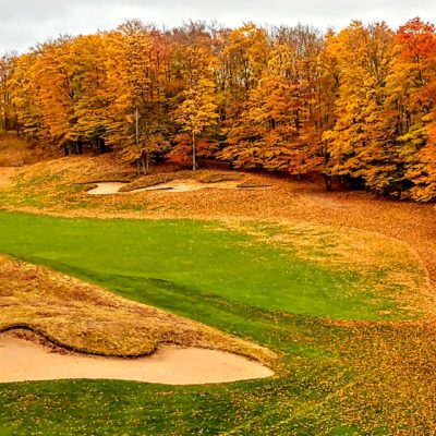 Gold and orange trees line a vibrant golf course green on a crisp fall day.