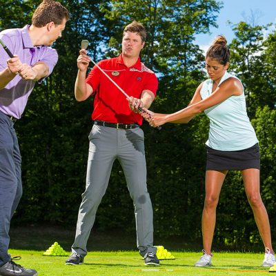 Male golf pro teaching a couple how to swing