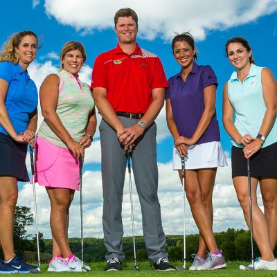 Male golf instructor standing with 4 female students holding golf clubs
