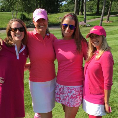 4 ladies wearing pink golf outfits