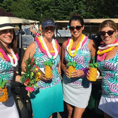 4 female golfers dress in tropical costumes