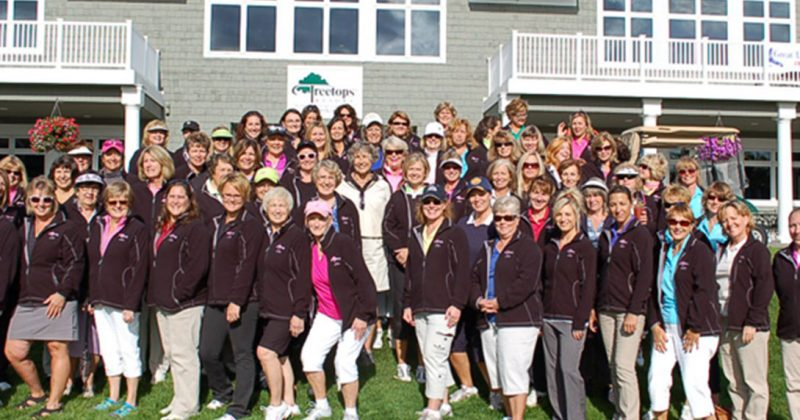 crowd of female golfers in matching black jackets