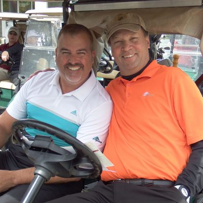 2 male golfers sitting in a cart