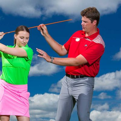 Golf pro teaching female golfer how to swing