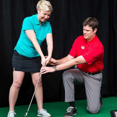 Golf pro instructing female student