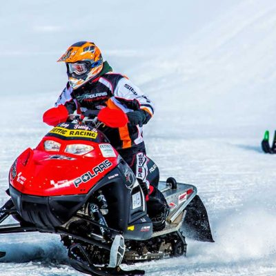 Person riding red snowmobile with a helmet on