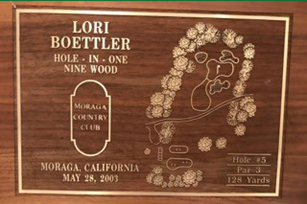 A wooden sign commemorating Lori Boettler's hole-in-one at Moranga Country Club's Hole 5 in 2003.