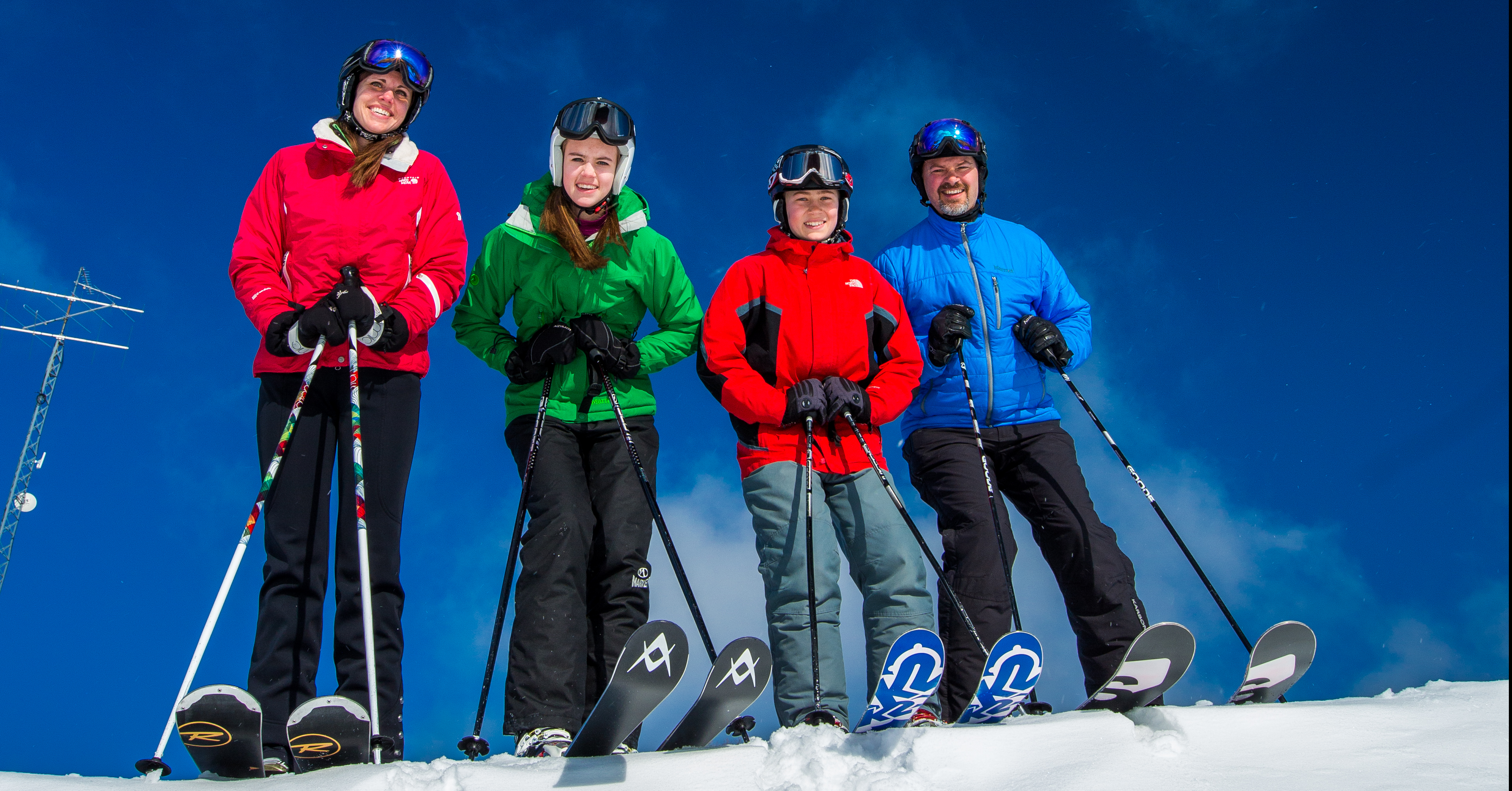 A group of four smiling people in full ski gear are ready to enjoy a sunny day on the slopes at Treetops Resort.