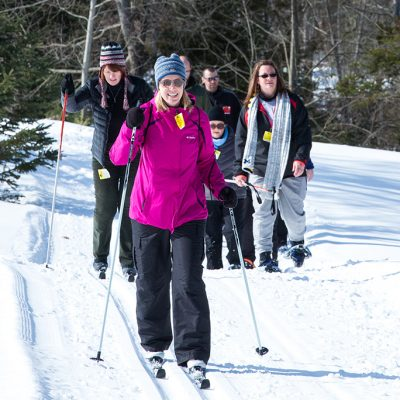 Group of women cross country skiing and snowshoeing on snowy trails at Treetops Resort in Gaylord Michigan