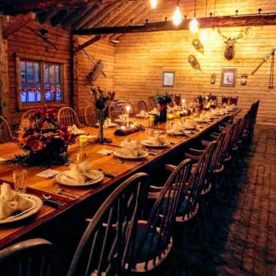 A large dining table lit with candles awaiting guests in a cabin setting at Treetops Resort.
