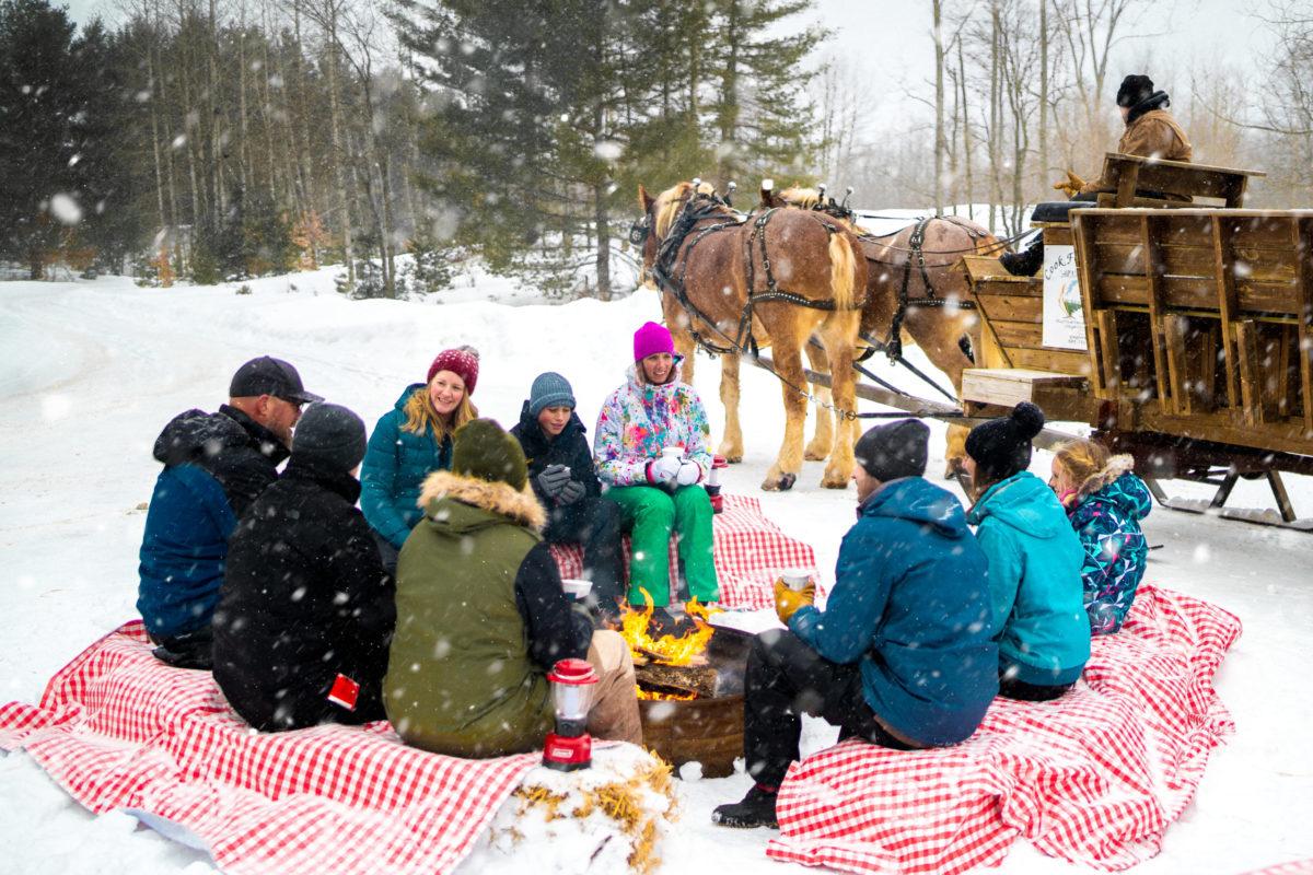 Wilderness Sleigh Ride Dinner Group Sitting Around a Fire
