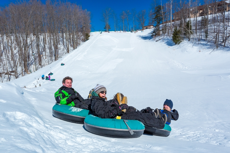 Three adults tubing down a snowy hill.