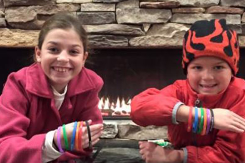 Two smiling children sit next to a fireplace with several bracelets on their arms at Treetops Resort.