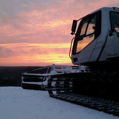 Snow groomer parked at the top of a ski hill at sunrise