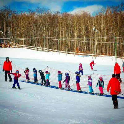 Small kids on a ski hill taking a ski lesson