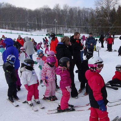 Dozens of small kids in ski gear at the bottom of a ski hill