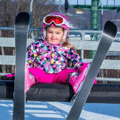 Young girl in pink snowsuit and goggles on a chairlift wearing skis