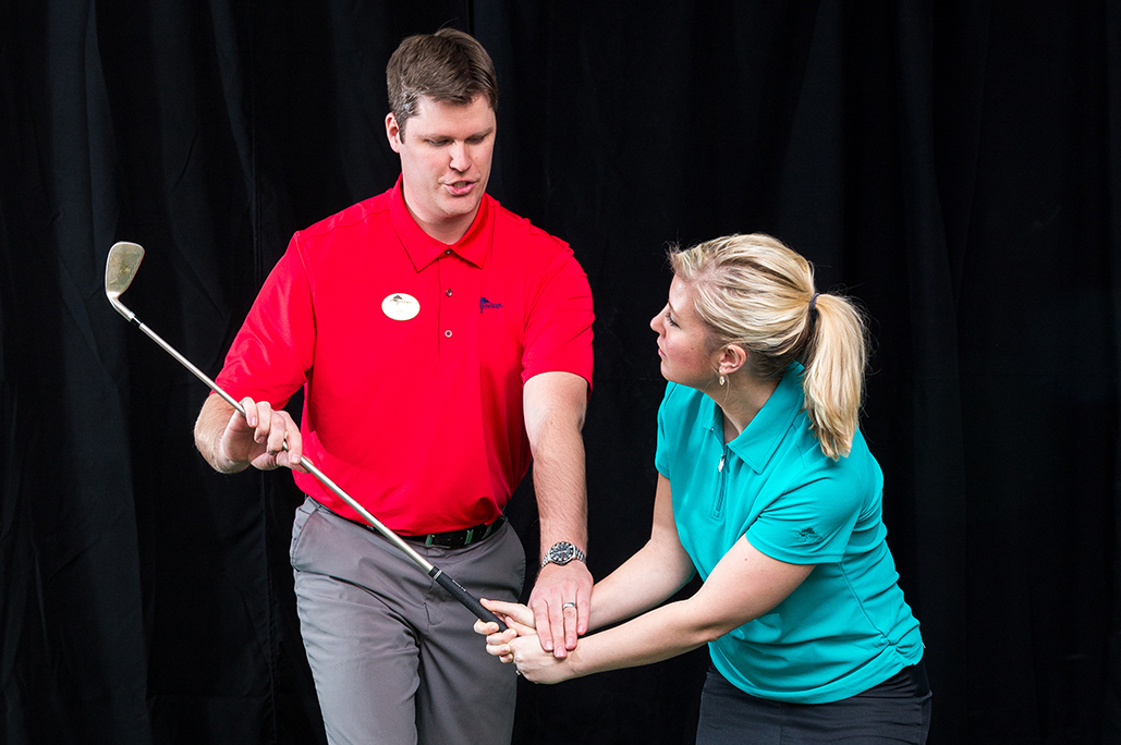 Male golf instructor in red shirt teaching female student